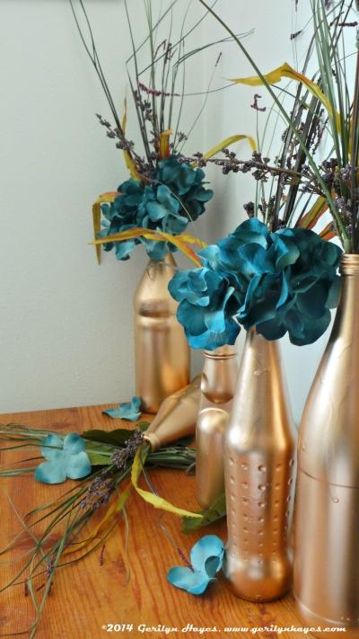 Floral arrangement, gold bottles. Gerilyn Hayes, www.gerilynhayes.com